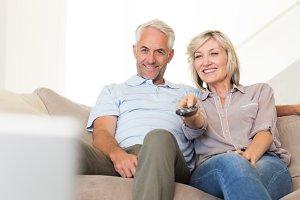 Happy couple watching tv on sofa