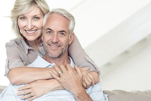 Smiling woman embracing mature man from behind on sofa