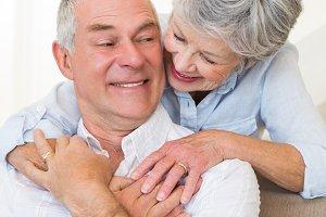Loving senior woman embracing husband