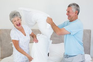 Senior couple having pillow fight in bed