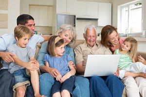 Multigeneration family using laptop in living room