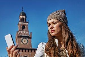 tourist woman near Sforza Castle, Milan taking selfie with phone