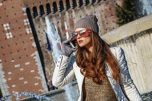 woman near Sforza Castle in Milan, Italy talking on smartphone