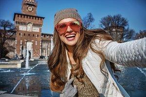 happy woman near Sforza Castle in Milan, Italy taking selfie