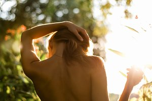Beautiful girl standing in forest, park topless naked back, straightens her hair, concept idea, your text ads a  figure, bright sun, enjoying summer vacation. Gentle background bokeh. Tanned skin. Life style
