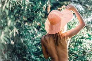 Beautiful girl standing in forest wearing a straw hat, topless park, conceptual idea, your text ads figure, gentle green background is blurred bokeh summer vacation. Tanned skin. Life style.