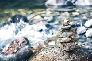 Stone pyramid cairn near river