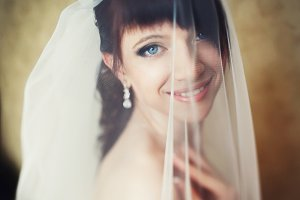 Pretty brunette smiles under a veil