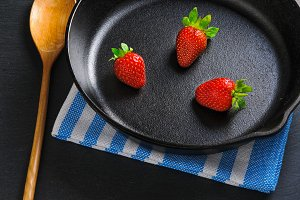 Three fresh red strawberries on black cast-iron pan served with wooden spoon and napkin. Concept