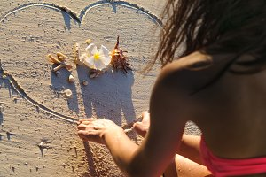 Girl at beach drawing heart on sand
