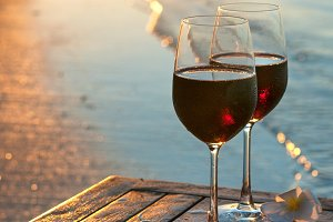 Romantic beach scene: two glasses of red wine at sunset near water