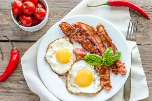 Fried eggs with bacon on the wooden