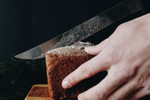 Hand cutting bread on wooden board
