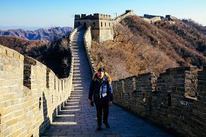 Asian man walking on Great wall of China - Travel in China, Asia concept
