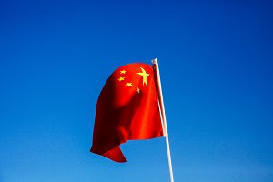 China flag waving over blue sky - country in Asia