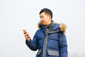 Asian man wearing winter jacket and using a smart phone over blue sky