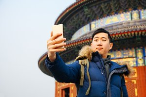 Asian man wearing winter jacket and using a smart phone over Chinese temple background (Selective focus)