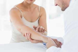 Male physiotherapist examining hand of woman