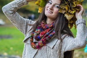 smiling, happy girl wearing a wreath of maple leaves