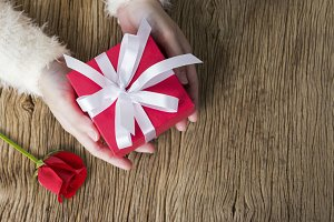 Woman holding gift box and rose