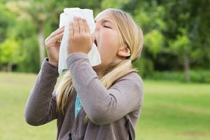 Girl sneezing into tissue paper at park