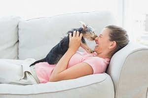 Happy woman playing with her yorkshire terrier on the couch