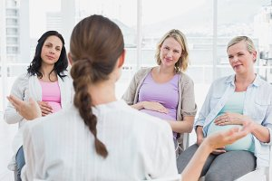 Pregnant women listening to gesturing doctor at antenatal class