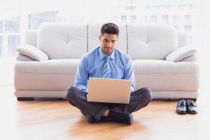 Businessman sitting on floor using laptop