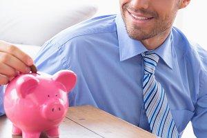 Handsome businessman putting change into piggy bank