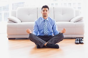 Businessman meditating in lotus pose on the floor