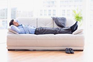 Tired businessman sleeping on a sofa