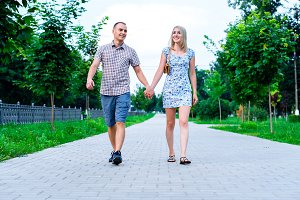 The guy with girl in a summer park holding hands walking relax, enjoy stroll, happy family concept slogan your text in background. City life. lot of greens.