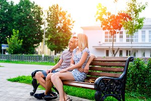 The guy with girl in a summer park sitting on  bench rest, enjoy meeting, happy family concept  slogan your text in background. City life.  holidays in country.