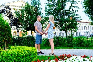 Young couple standing in park ribbon holding each other's hands, a declaration of love,  gentle hug, concept    family,  happy marriage. Lifestyle in the city. Outdoors.