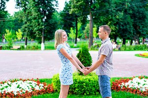 Young couple standing in park ribbon holding each other's hands, a declaration of love,  gentle hug, concept  family,  happy marriage. Lifestyle in city. Outdoors.