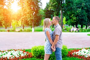 Young couple standing in park ribbon holding each other's hands kiss, a declaration of love, gentle hug, concept family, happy marriage. Lifestyle in the city. Outdoors.
