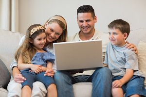 Family using laptop together on sofa
