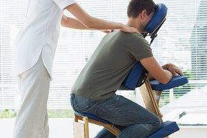 Man receiving shoulder massage from therapist