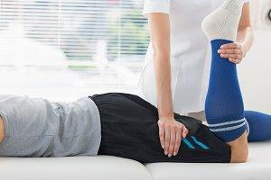 Physiotherapist working on leg of man