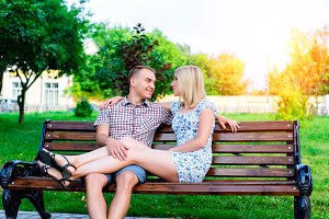 Young couple man and woman sitting on a bench hugging in park ribbon,  declaration of love,  gentle hug, the concept  event  family, happy marriage. Lifestyle in the city. Outdoors.