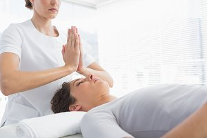 Therapist giving Reiki treatment to woman