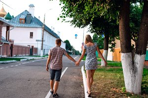 man and woman hold each other's hand, summer in city, concept of event young family, newlyweds complex relationship. Lifestyle in romance. Outdoors.