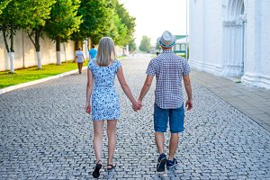 Man and woman are on stone pavement holding hands, summer in city, concept of the event young family, newlyweds complex relationship. Lifestyle in romance. Outdoors.