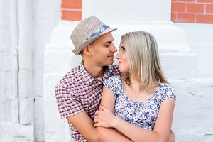 Young couple, looking at each other a bright sunny day in city of great outdoors, happy family concept, idea good relationship. Smile and smotryad  . Against background   white brick wall.