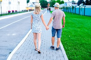 Man and woman stone pavement holding hands, summer in city, concept of the event young family, newlyweds complex relationship. Lifestyle in romance. Outdoors.