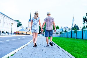 Man and woman are on stone pavement holding hands, summer in city, concept of event young family, newlyweds complex relationship. Lifestyle in romance. Outdoors.