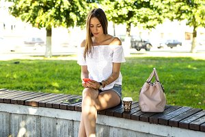 Beautiful brunette girl sitting on a park bench with  telephone, SMS writes and reads social networks. Resting in the fresh air.