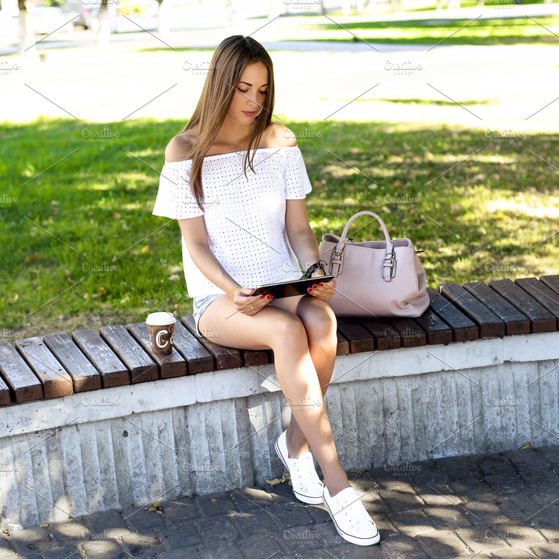 Beautiful brunette girl sitting on a park bench with the tablet, watching  movie, reading book, puts Like social networks  Resting in the shadow of  the