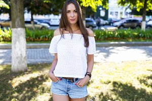 beautiful girl standing in  park, in  white jacket denim shorts, fashion style urban life,  bright sunny summer day. Outdoors brunette woman. Sensually looking eyes.