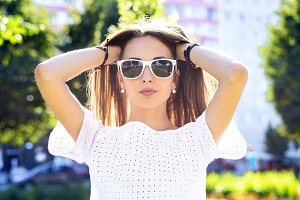 Beautiful young girl in glasses summer corrects hair, fashion style urban life. Brunette in the park bright  day outdoors.